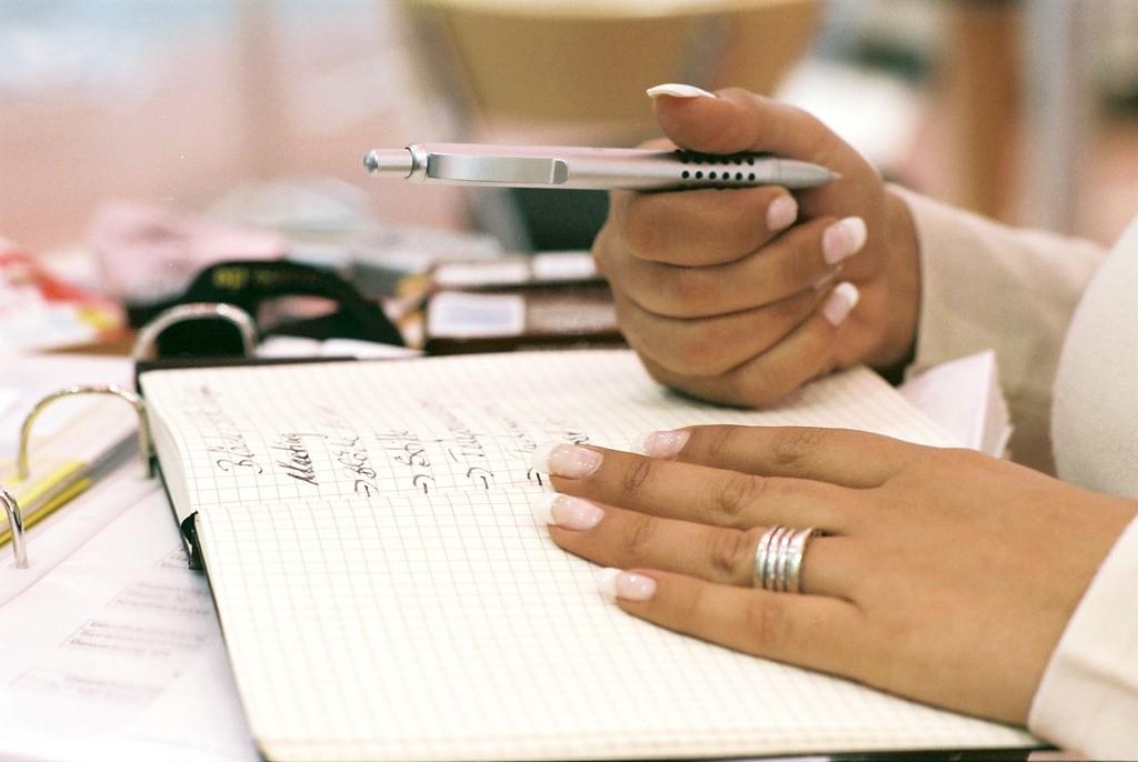 Foto zweier Hände mit Notizbuch und Kugelschreiber