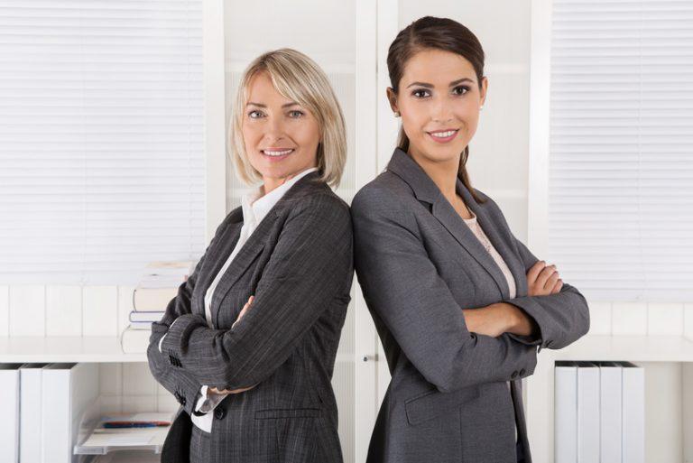 Foto zweier lachender Frauen, Rücken an Rücken stehend