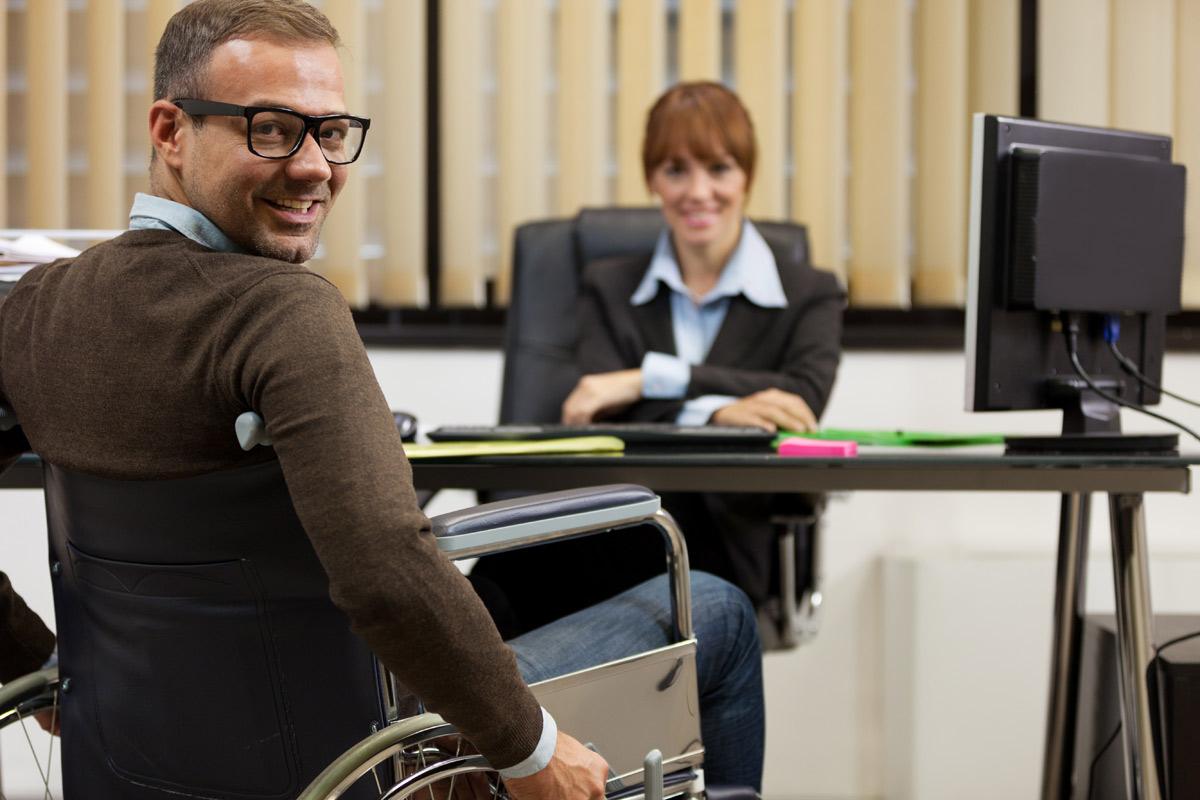 Foto, zwei Menschen am Schreibtisch einer davon im Rollstuhl