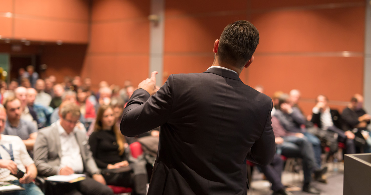 Foto: Redner vor gefülltem Saal