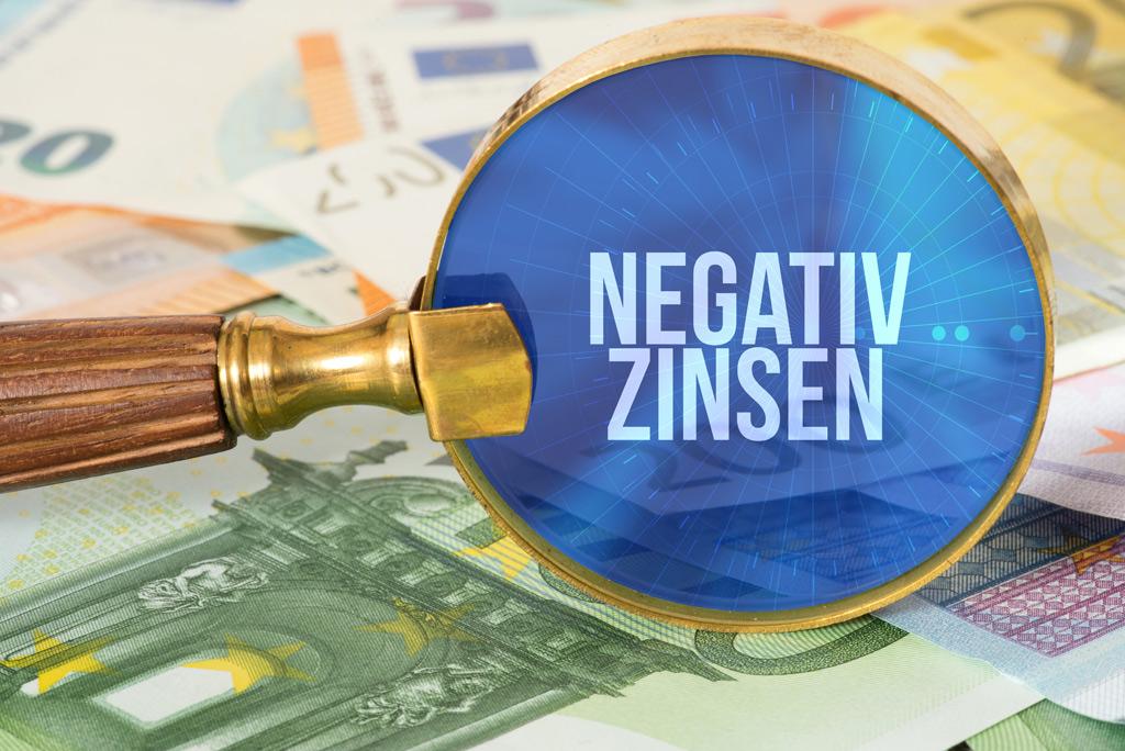 Grafik: Lupe zeigt auf Schrift Negativ Zinsen