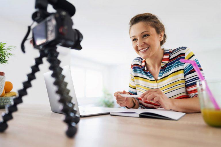 Frau vor Notebook und Kamera