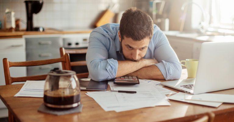 Foto: Mann zusammengesunken am Küchentisch mit Notebook
