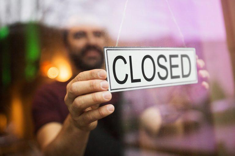 Foto: Mann hängt Schild an Tür mit Aufschrift Closed
