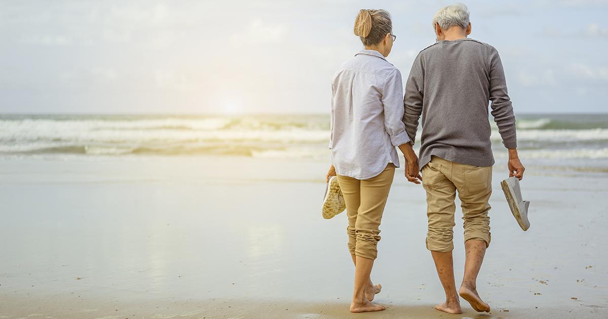 Foto: älteres Paar am Strand von hinten fotografiert