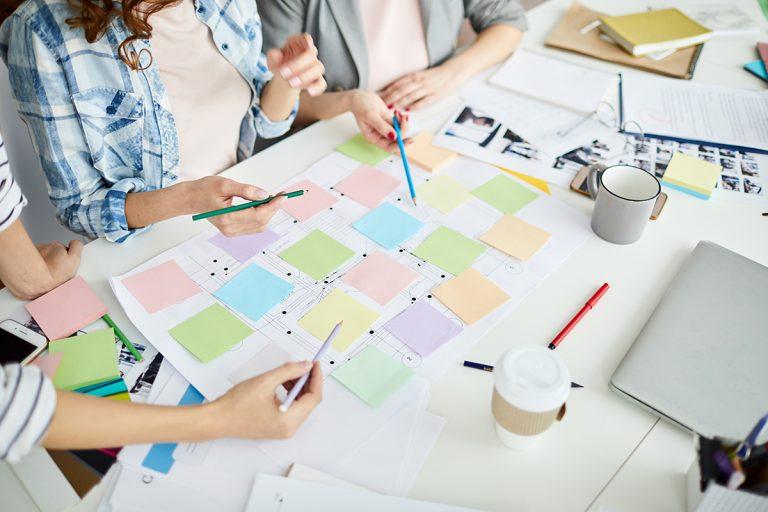 Foto: Menschen rund um Tisch planen Projekt